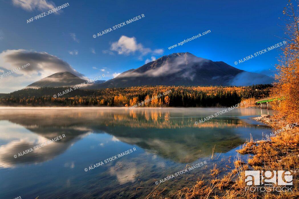 Stock Photo: Fall colors and the Kenai Mountains reflecting on a misty Kenai Lake at Cooper Landing, Kenai Peninsula, Southcentral Alaska, Autumn, HDR.