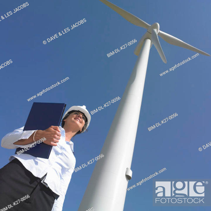 Stock Photo: Low angle view of female engineer by wind turbine.