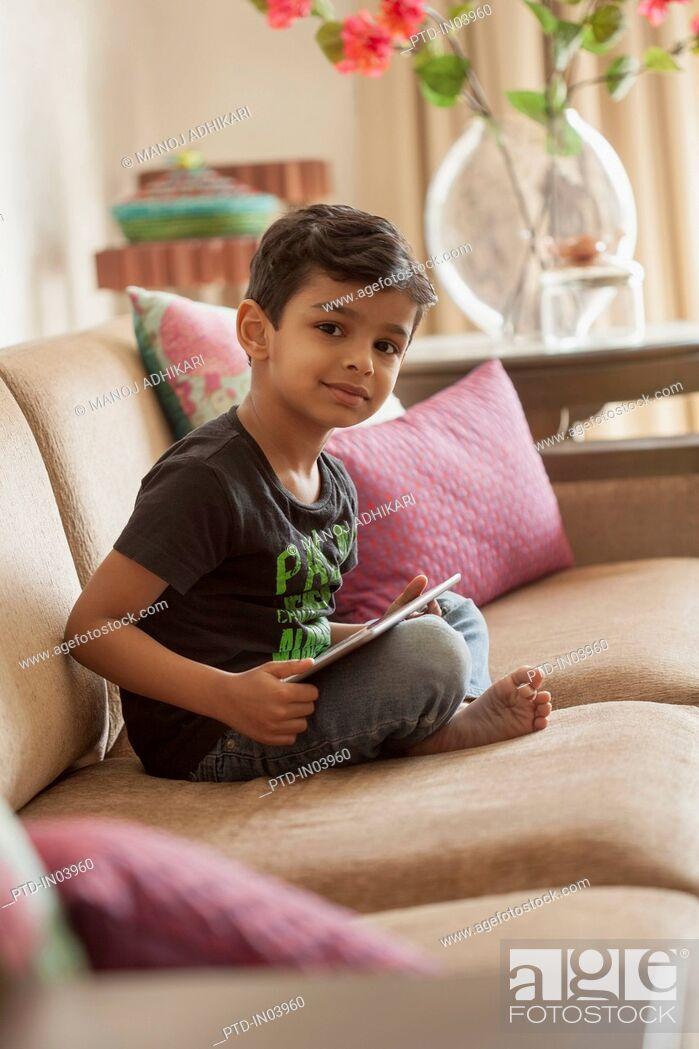 Stock Photo: India, Little boy (4-5) sitting cross legged on sofa using digital tablet.