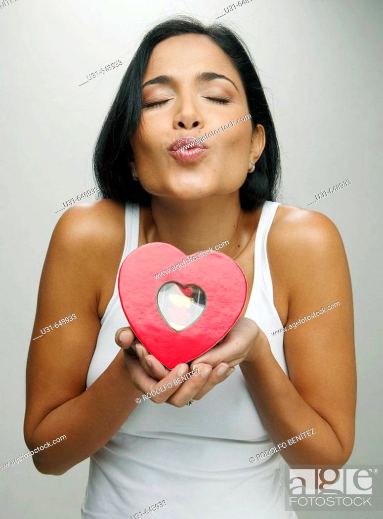 Stock Photo: Latin girl blowing a kiss giving a valentine's chocolate heart.