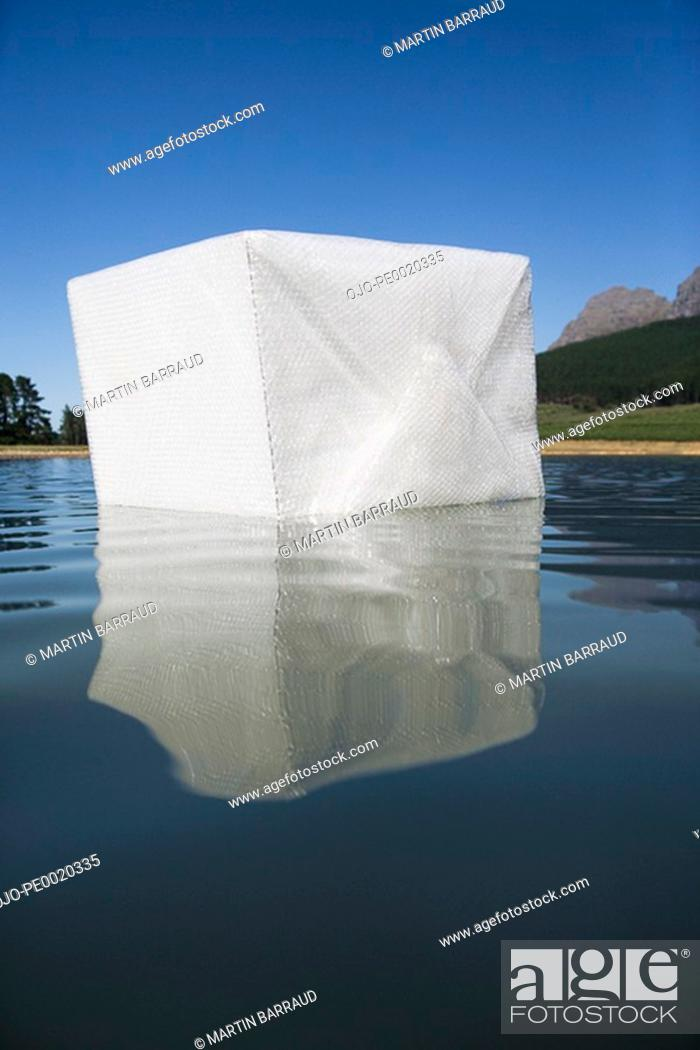 Stock Photo: Box floating in water with trees.