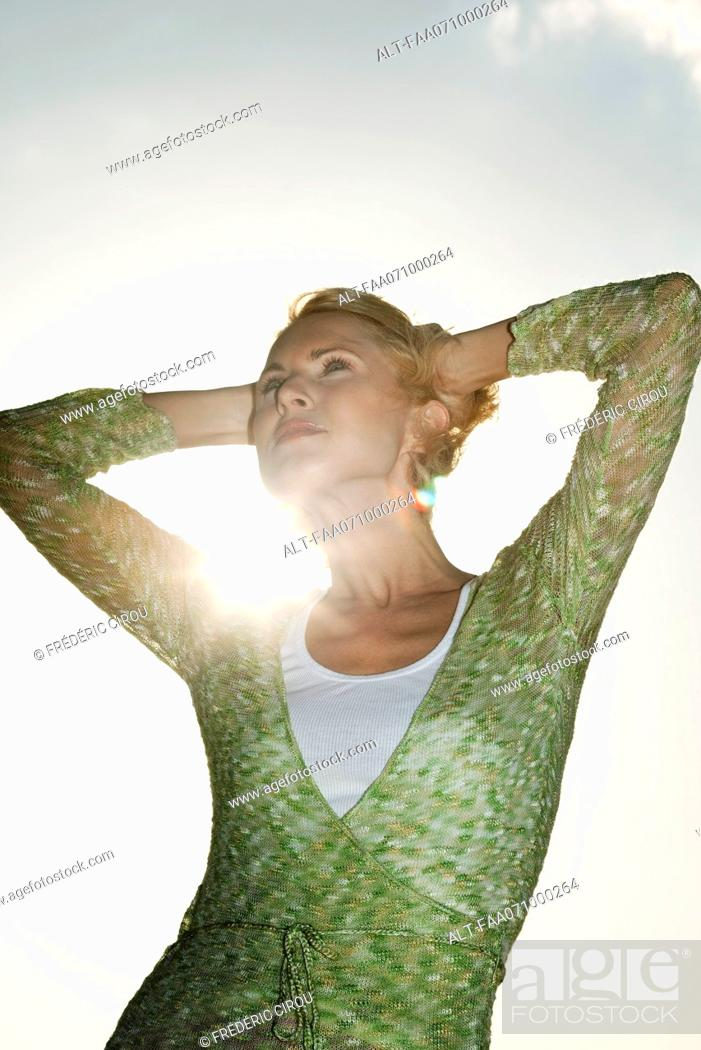 Stock Photo: Woman with hands behind head contemplating outdoors.
