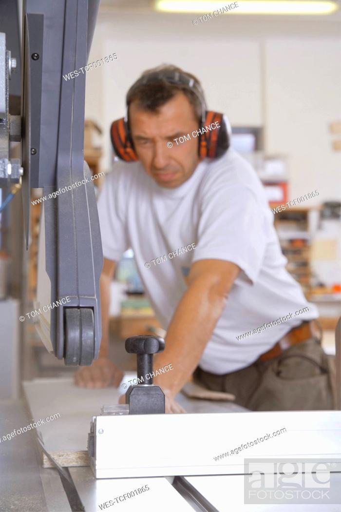 Stock Photo: Germany, Upper Bavaria, Schaeftlarn, Carpenter working on sawing machine.