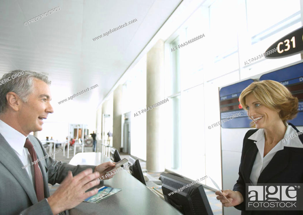 Stock Photo: Businessman at airline check-in counter.