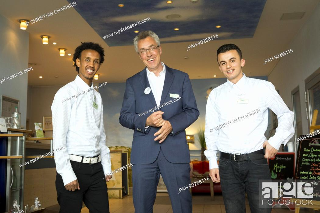 best quality sneakers footwear Hotel director Gabor Hnizdo (c) poses with the two refugees ...