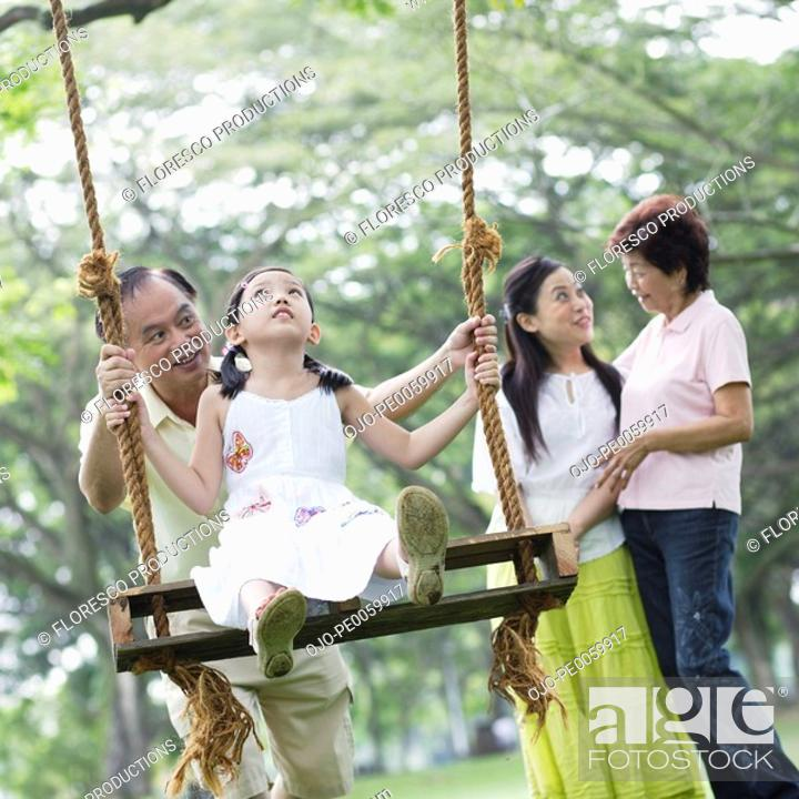 Stock Photo: Family outdoors at park with young girl on swing.