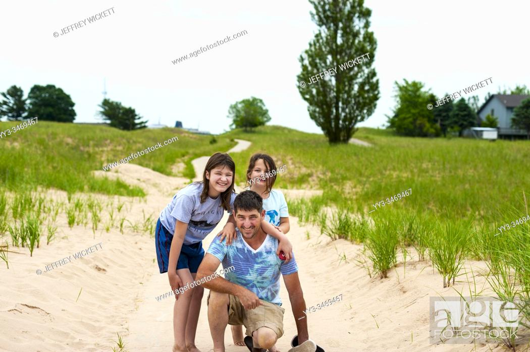 Stock Photo: Father and daughers posing on dunes trail in Ludington, Michigan, USA. .