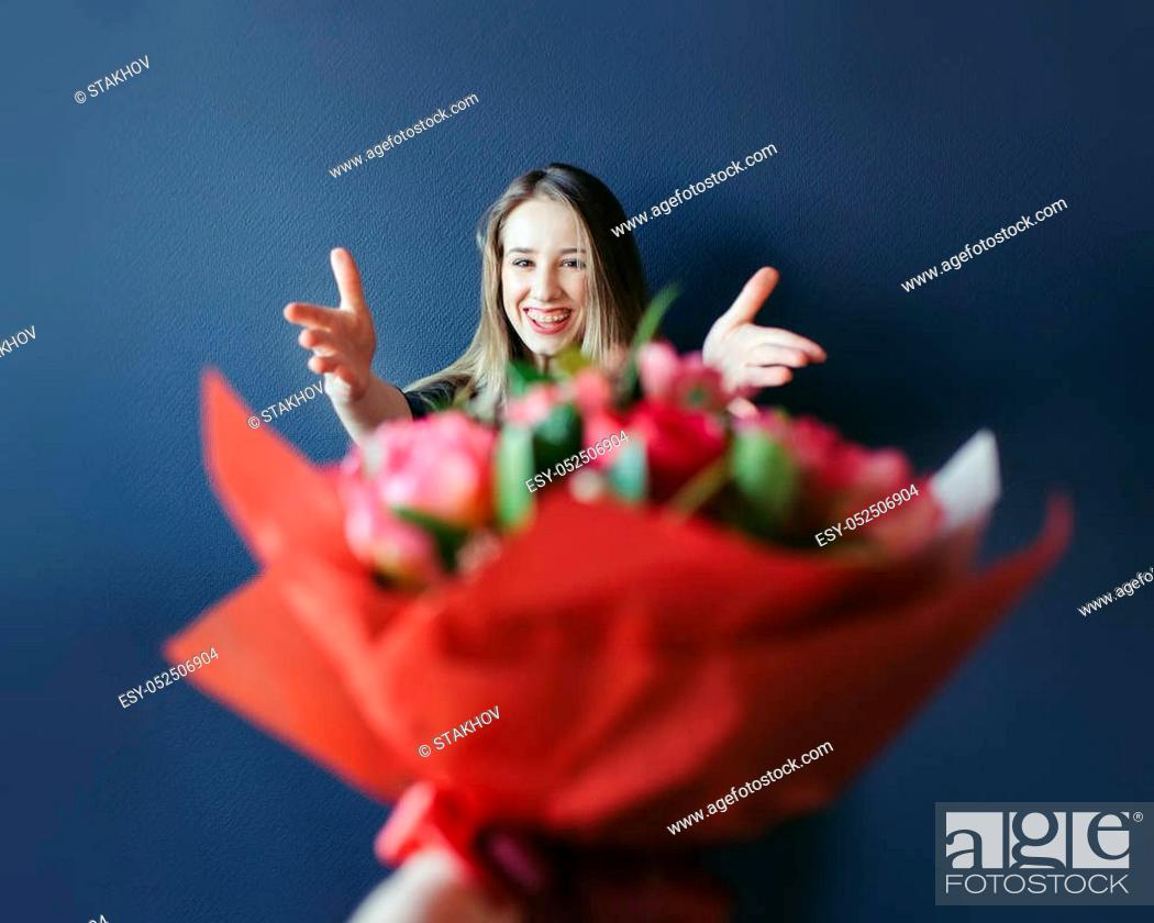 Stock Photo: Before date. Girlfriend getting bouquet of red tulips. Boyfriend giving tulips gift present to his girl.