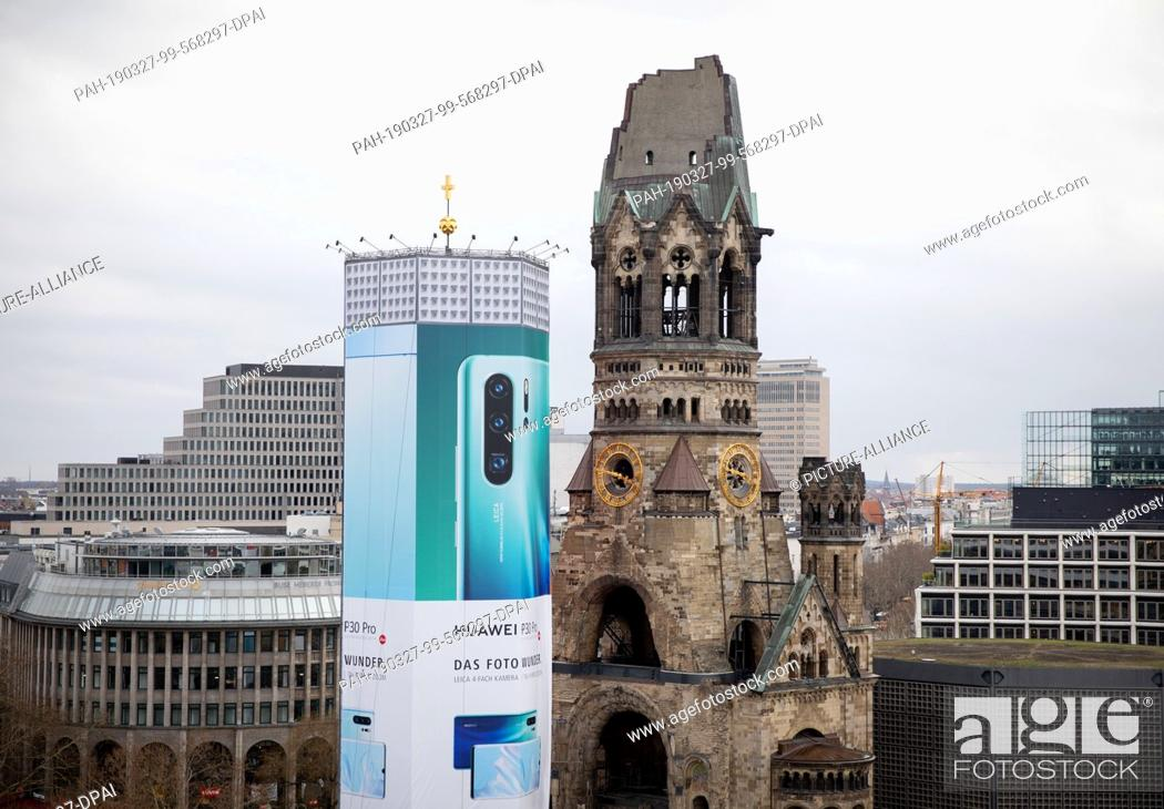 Stock Photo: 27 March 2019, Berlin: A huge advertising banner hangs on the bell tower of the Berlin Gedächtniskirche. For six months, the tower will be covered by.