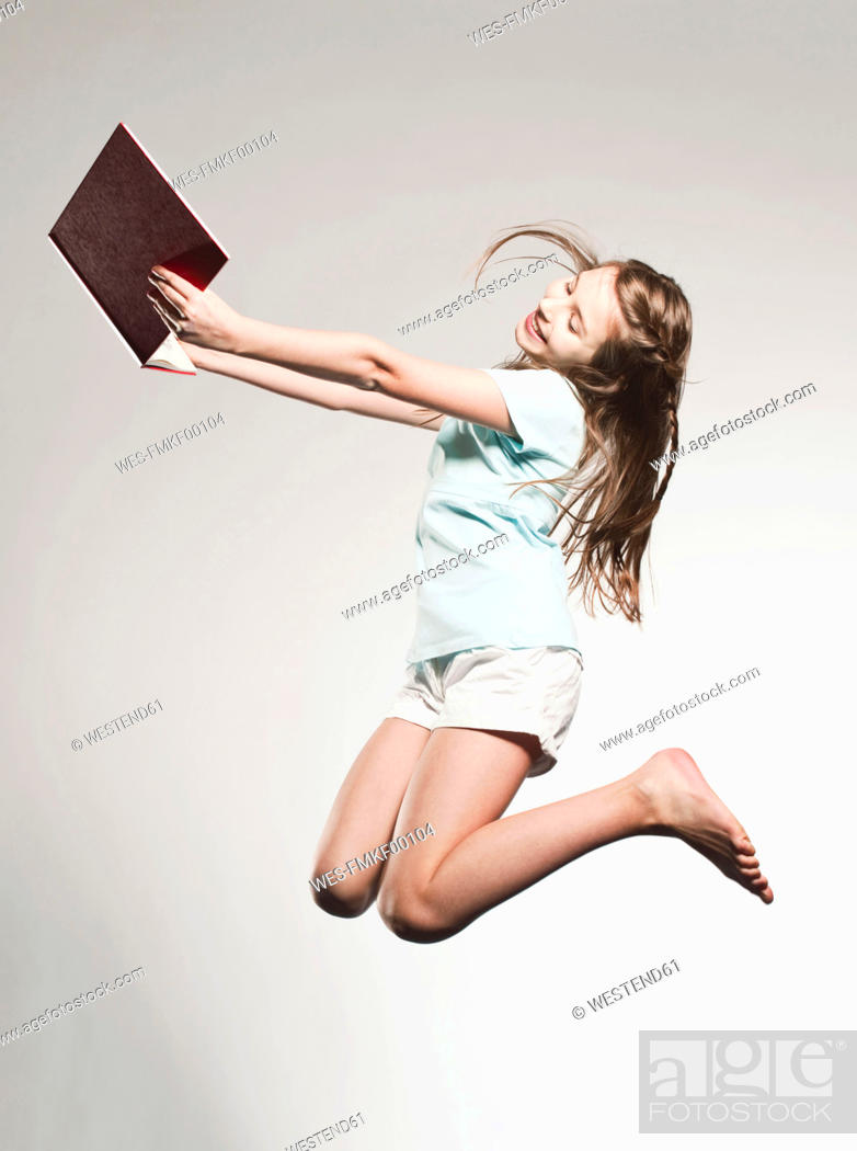 Stock Photo: Girl 10-11 holding book and jumping, smiling.