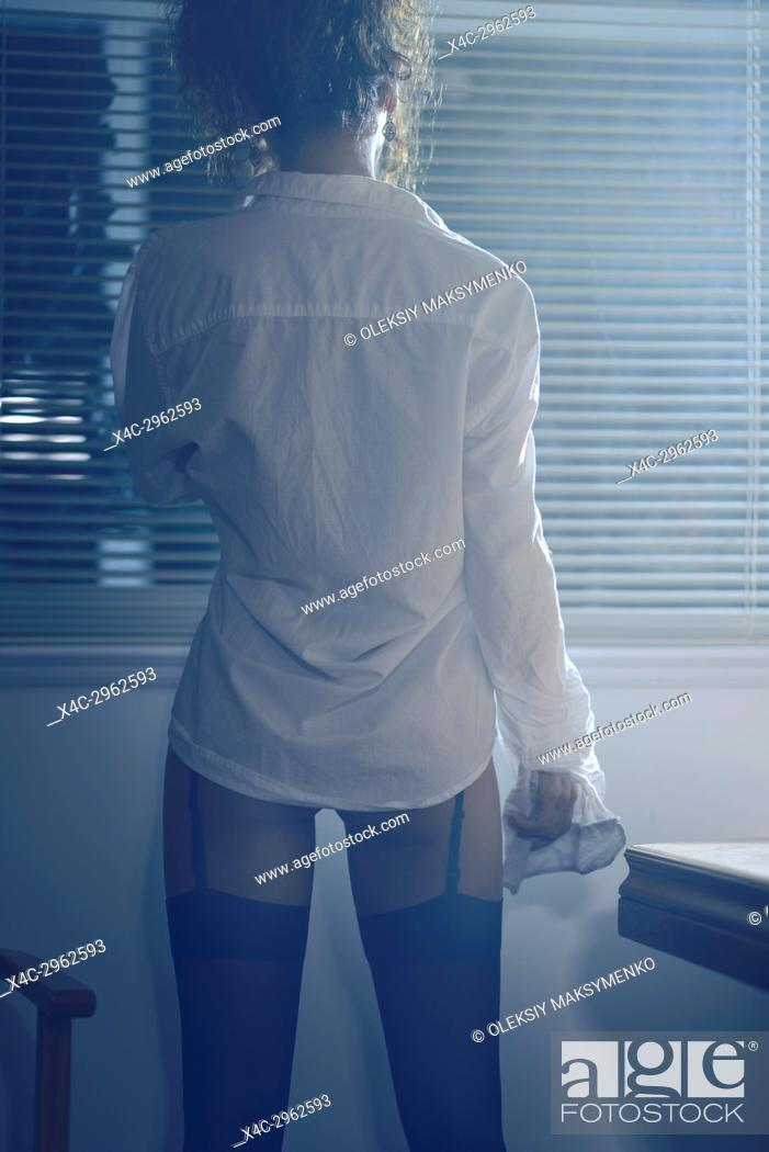 Stock Photo: Back of a sexy woman wearing a white men's dress shirt and black stockings looking out of the window at night.