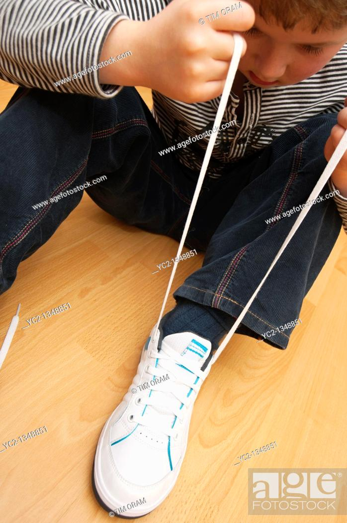 Stock Photo: A picture of a seven year old boy learning to tie his shoelaces in the Uk.