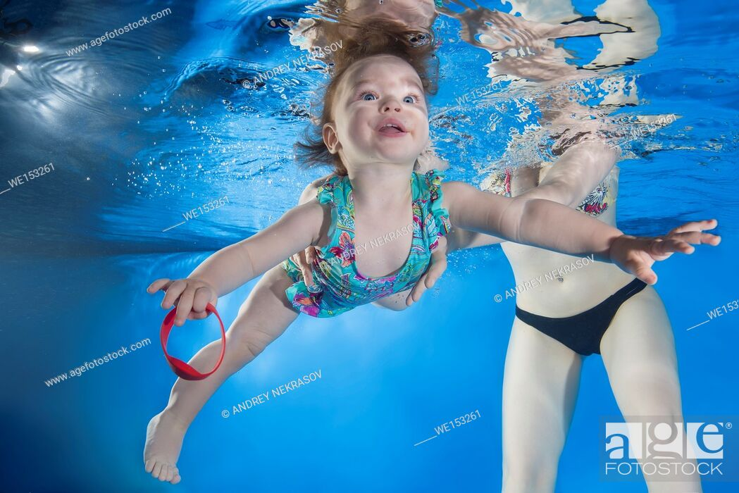 Stock Photo: Mom teaches a little girl to swim under water.