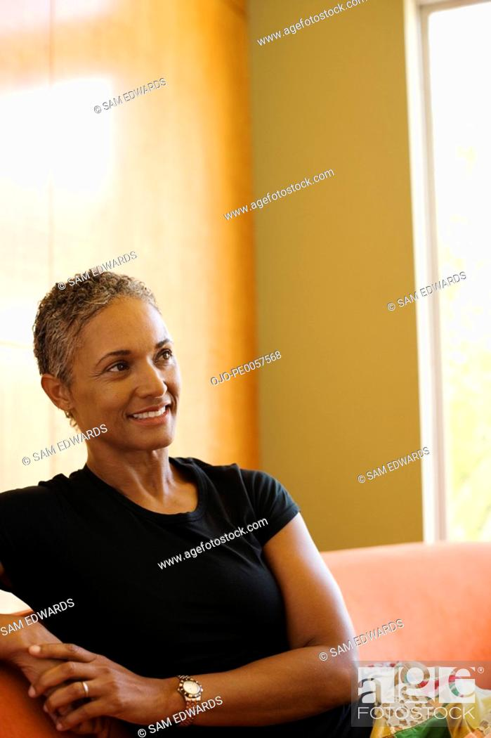 Stock Photo: Woman sitting on sofa in modern home.