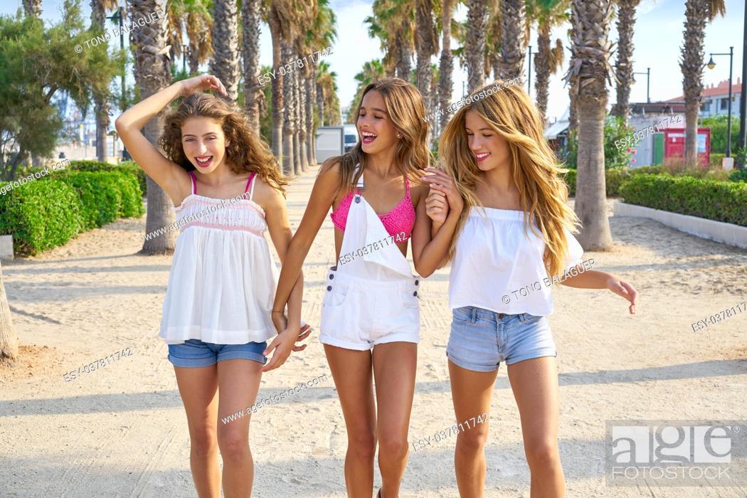 Photo de stock: Teen best friends girls group walking happy in a palm trees beach area.