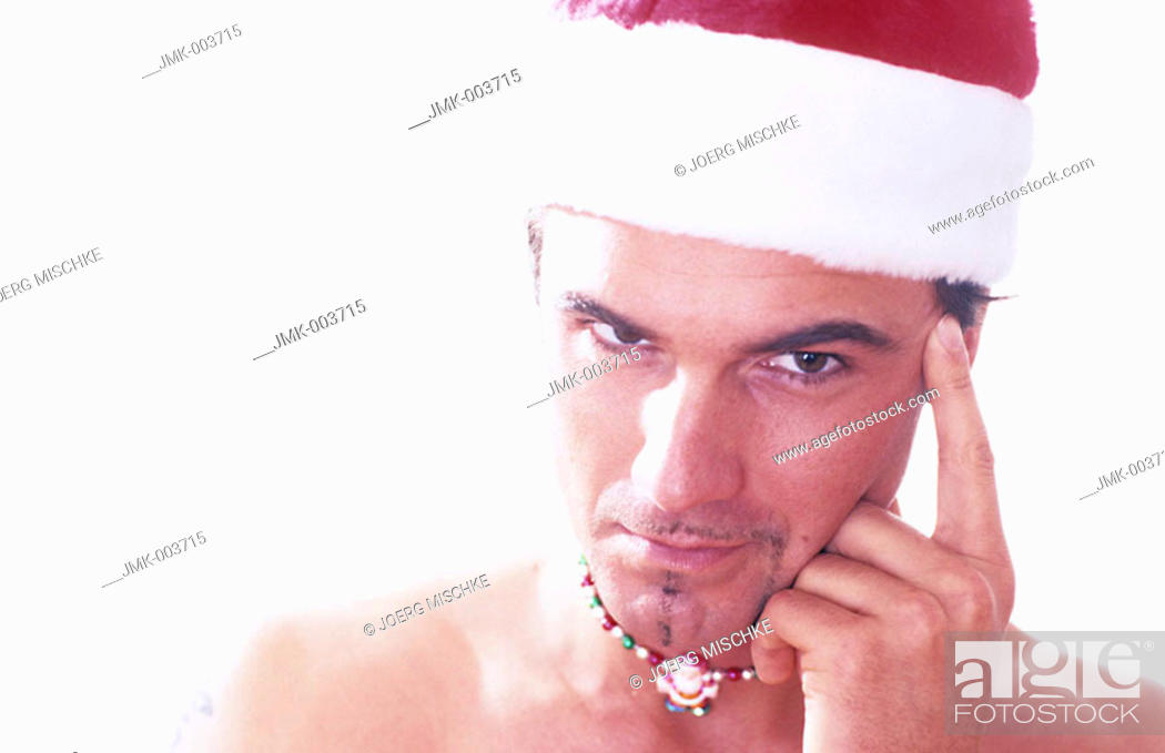 Stock Photo: A young man, 20-25 25-30 30-35 years old, stripped to the waist, wearing a Santa Claus cap and a necklace.