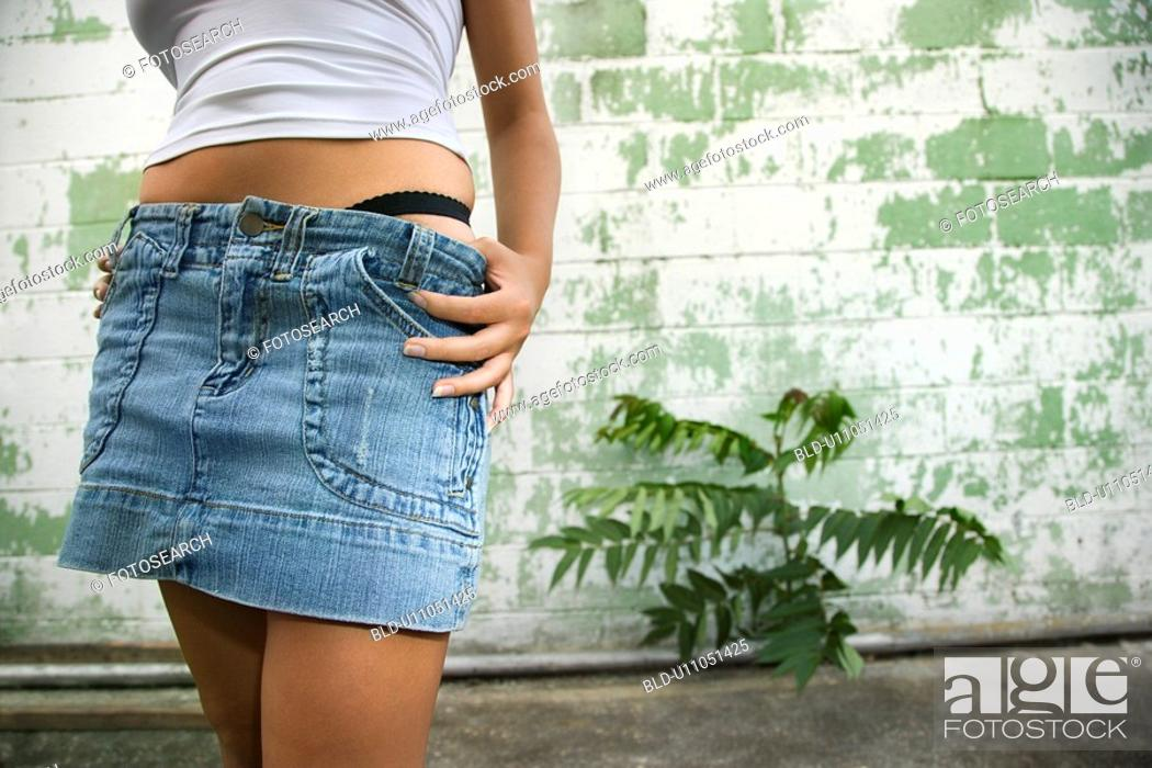 Stock Photo: Torso shot of mid-adult blonde woman wearing blue jean mini skirt with underwear showing beside building in alley.
