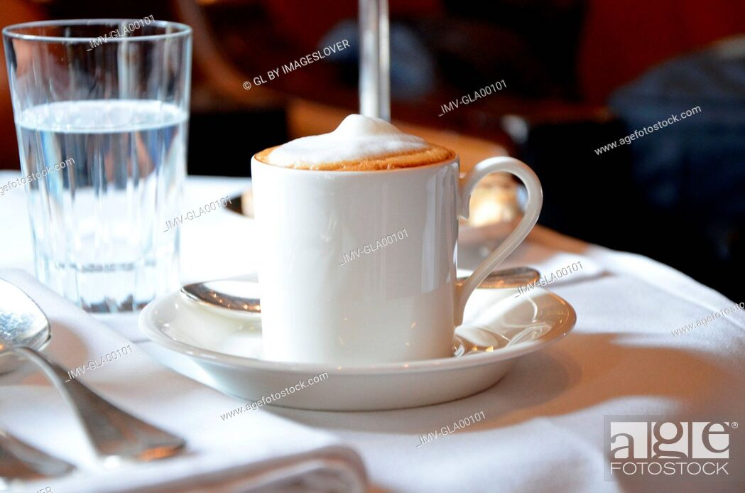 Imagen: Cup of cappuccino on saucer with spoon.