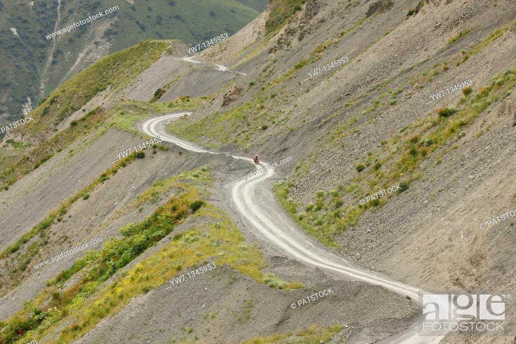 Stock Photo: Female cyclist on a winding mountain road, Kyrgyzstan.