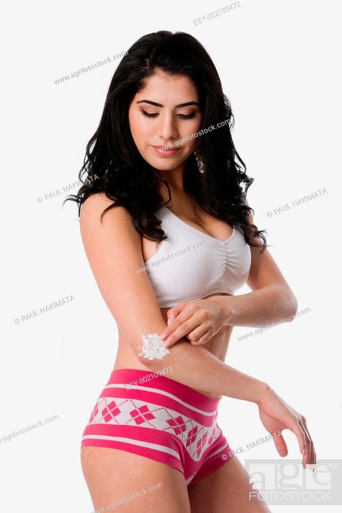 Stock Photo: Beautiful young woman applying exfoliating moisturizing cream on dry elbow skin, isolated.
