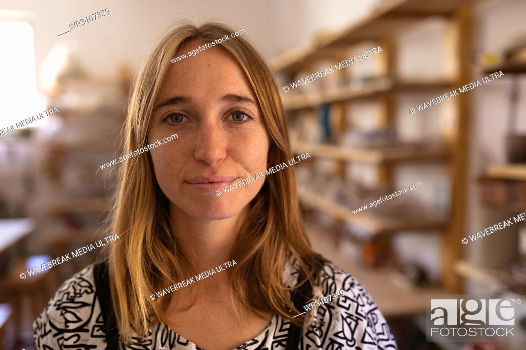 Stock Photo: Portrait close up of a young Caucasian female potter standing in a pottery studio.