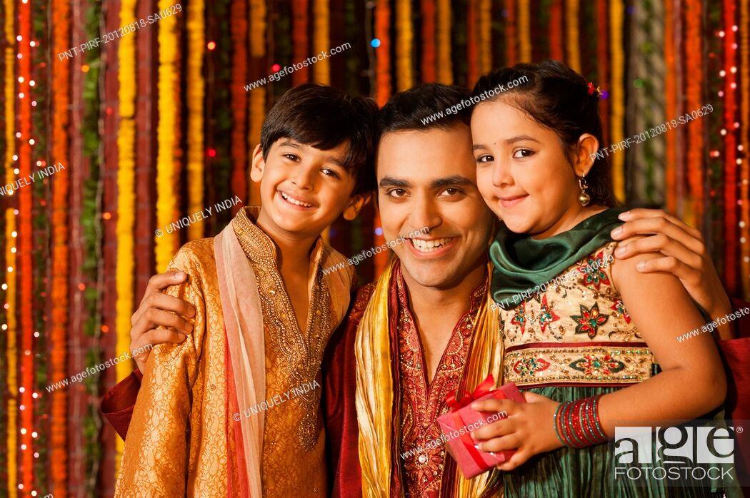 Stock Photo: Man hugging his children on Diwali.