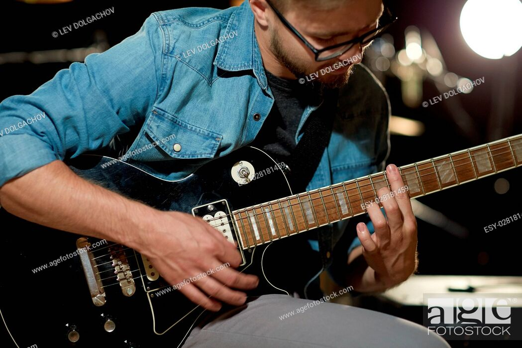 Stock Photo: music, people, musical instruments and entertainment concept - close up of male guitarist playing electric guitar at studio rehearsal.