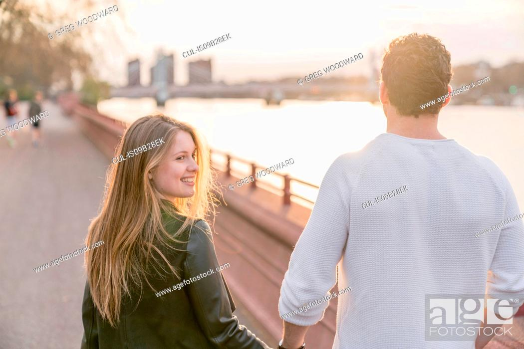 Stock Photo: Rear view of couple strolling on waterfront at sunset, Battersea Park, London, UK.