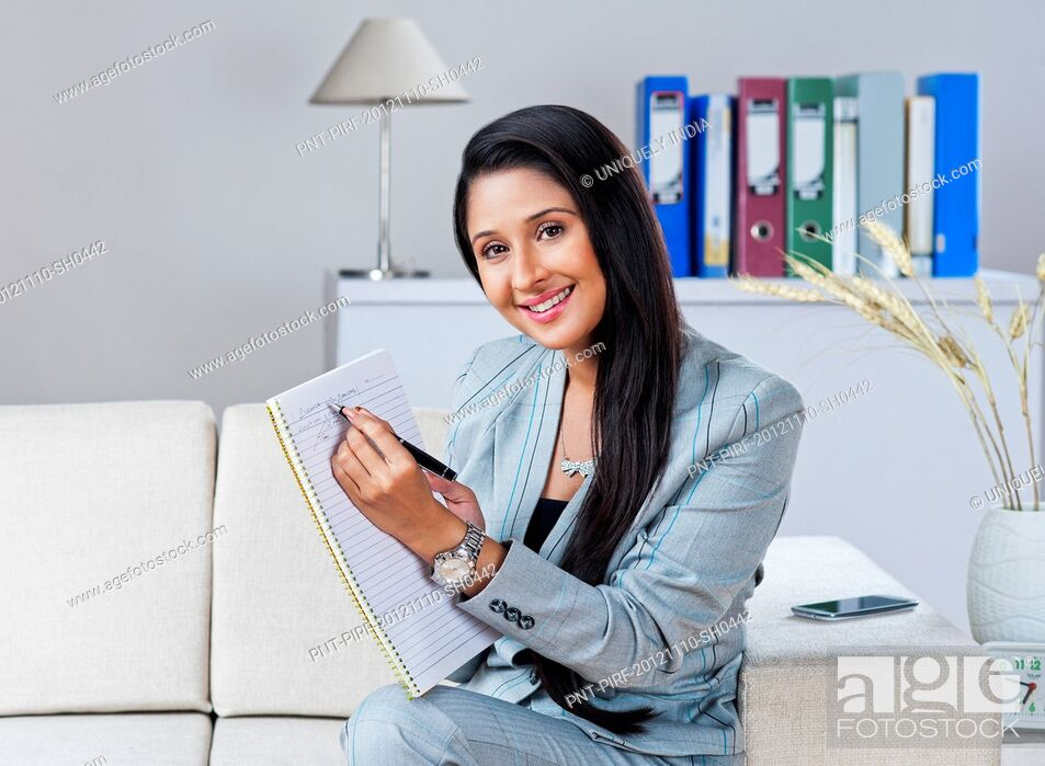 Stock Photo: Businesswoman sitting on a couch and writing on a notebook.
