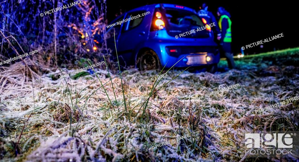 Stock Photo: 01 January 2020, Esslingen, Aichwald-Aichschiess: After a black ice accident, a vehicle is parked beside the road on a meadow covered with hoarfrost.