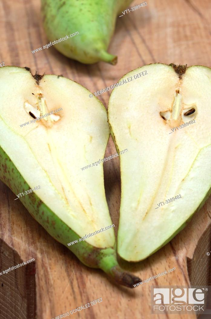 Stock Photo: pear split in two on wood board for backgrounds and textures.
