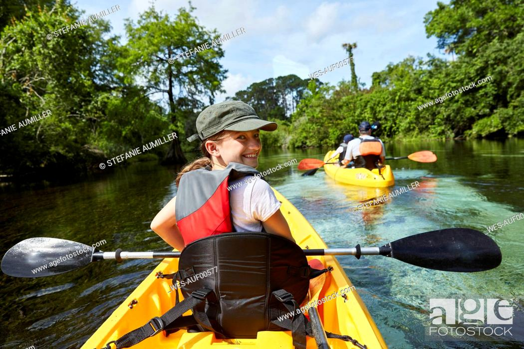 Stock Photo: Smiling girl canoeing in lake during vacations.