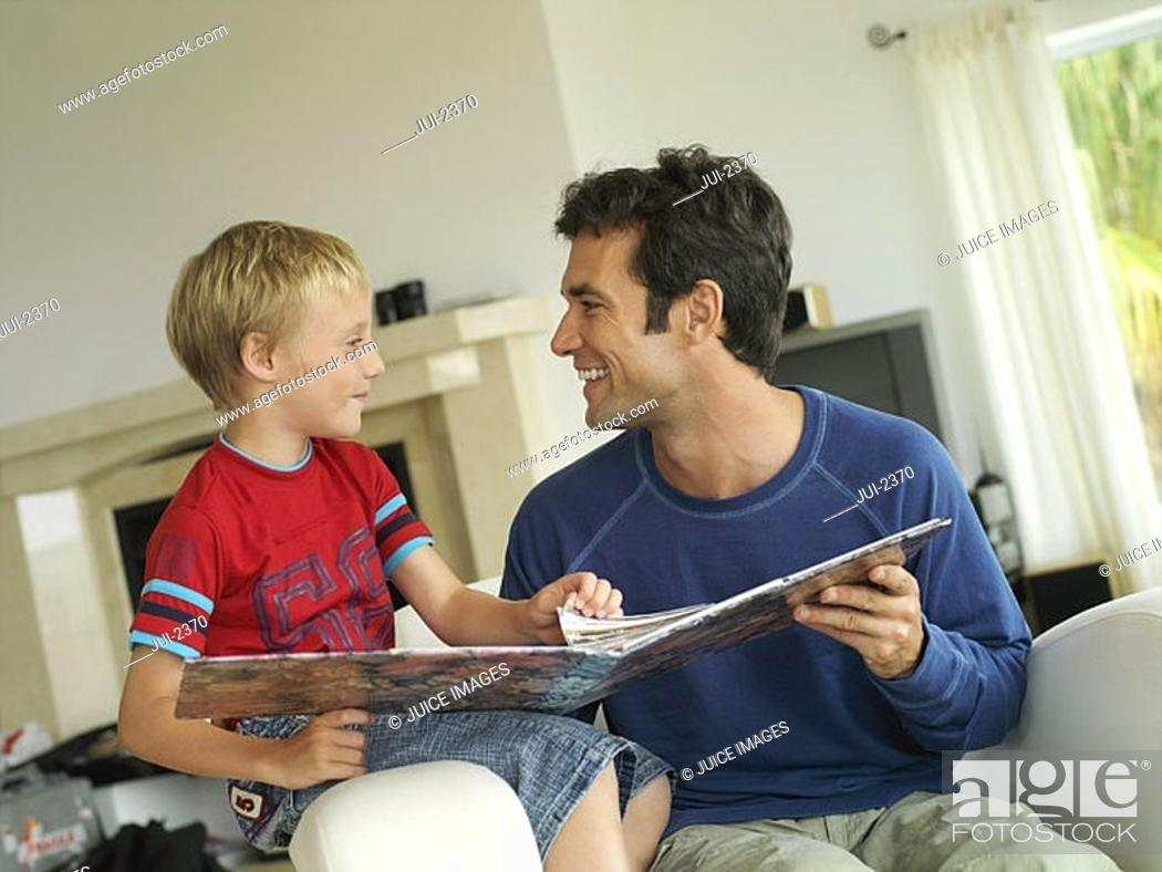 Stock Photo: Father and son 5-7 looking at photo album at home, sitting in chair, face to face, smiling tilt.