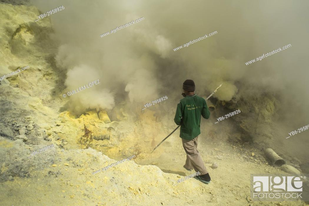 Stock Photo: A miner extract sulfur rocks from the Kawah Ijen crater in East Java, Indonesia.