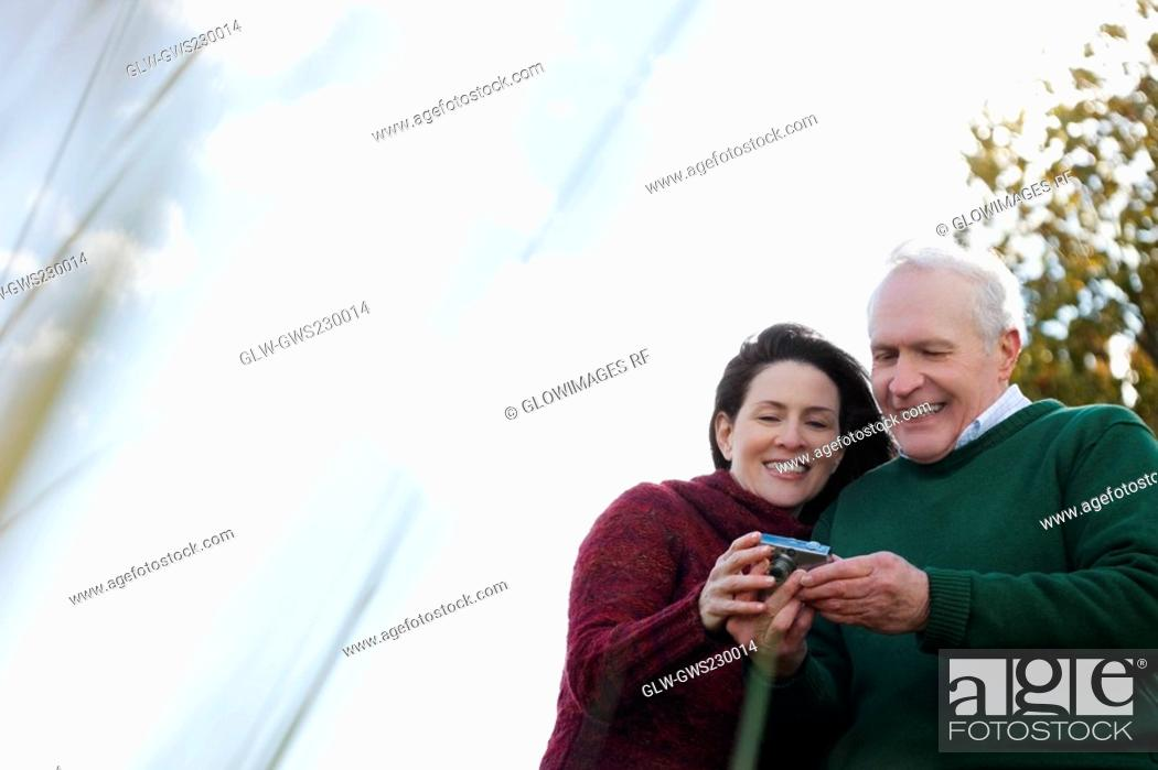 Stock Photo: Couple looking at a digital camera and smiling.