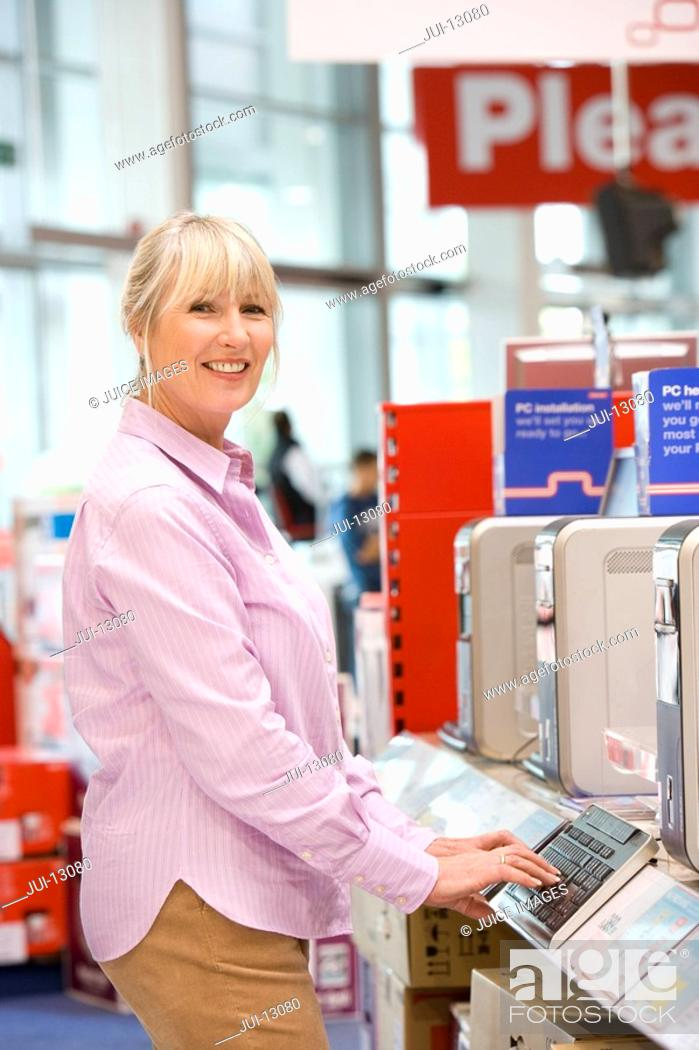 Stock Photo: Mature woman shopping for computer, smiling, portrait.