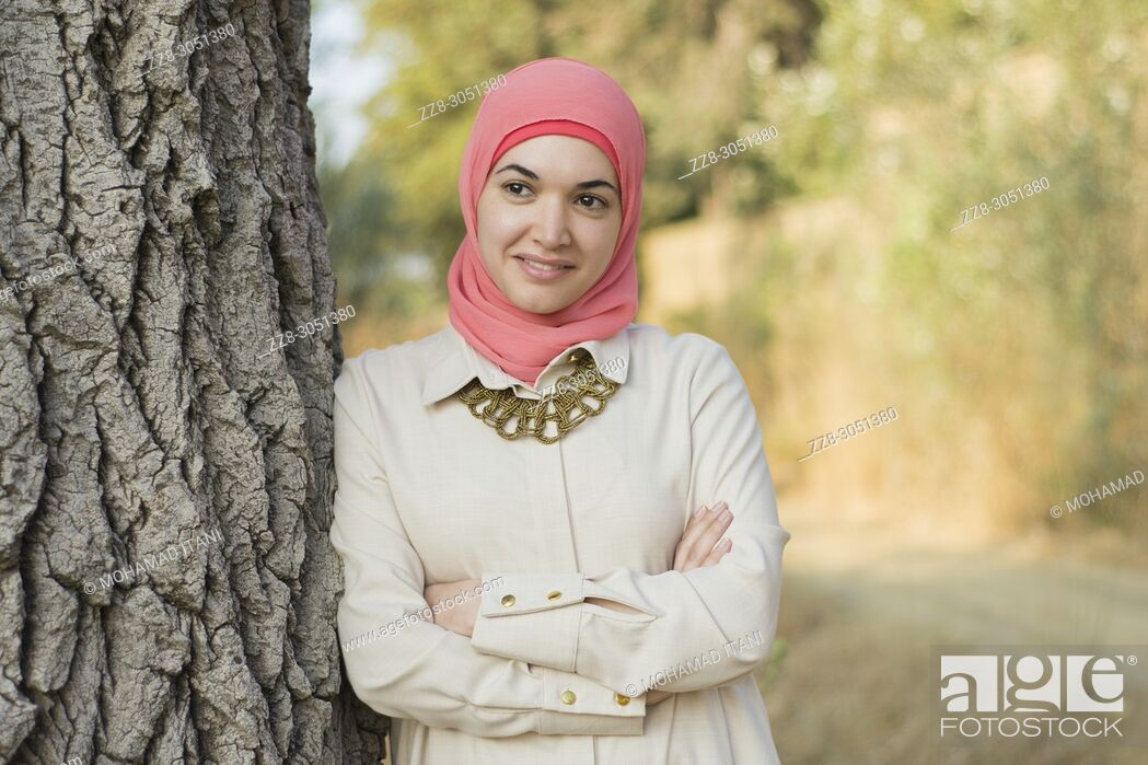 Stock Photo: Happy Muslim woman wearing Hijab leaning against a tree looking away.