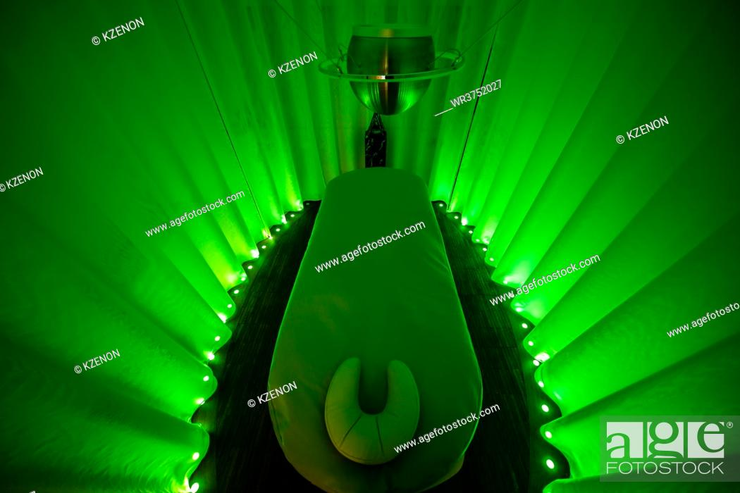 Stock Photo: Spa room with green lights and massage bed.