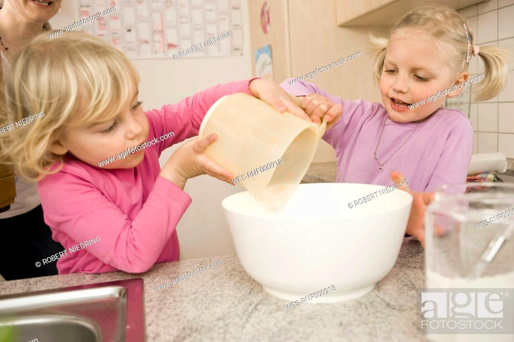 Stock Photo: Sisters making cake in kitchen.