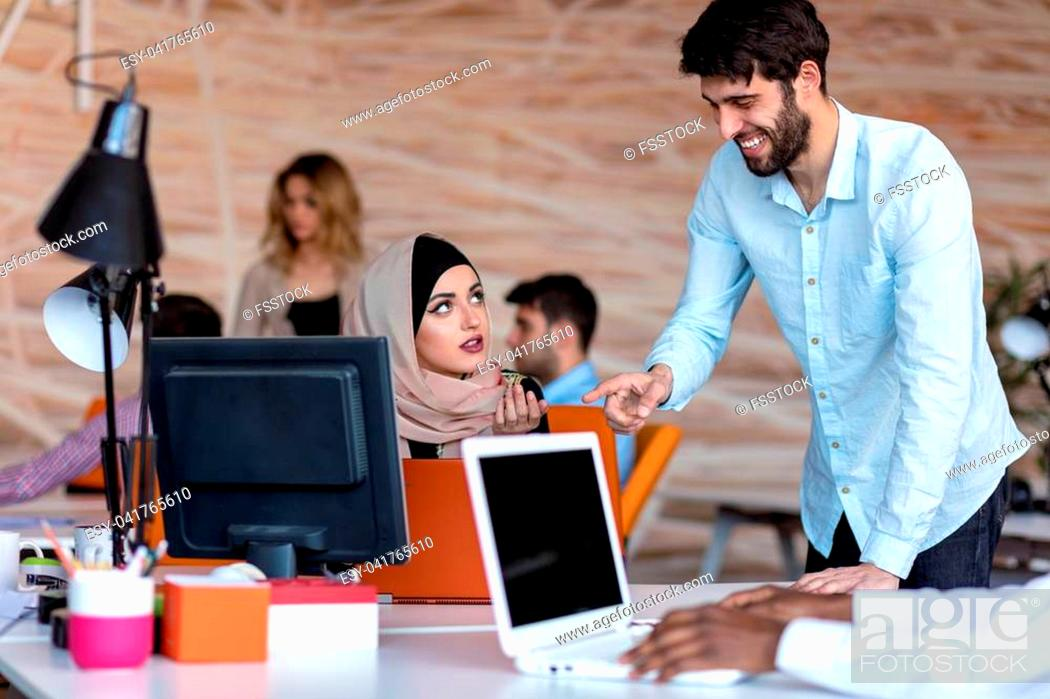 Stock Photo: diverse college students using laptop and talking, learning exchanging ideas.