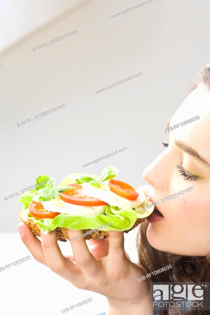 Stock Photo: Young woman eating mozarella and tomatoe sandwich.