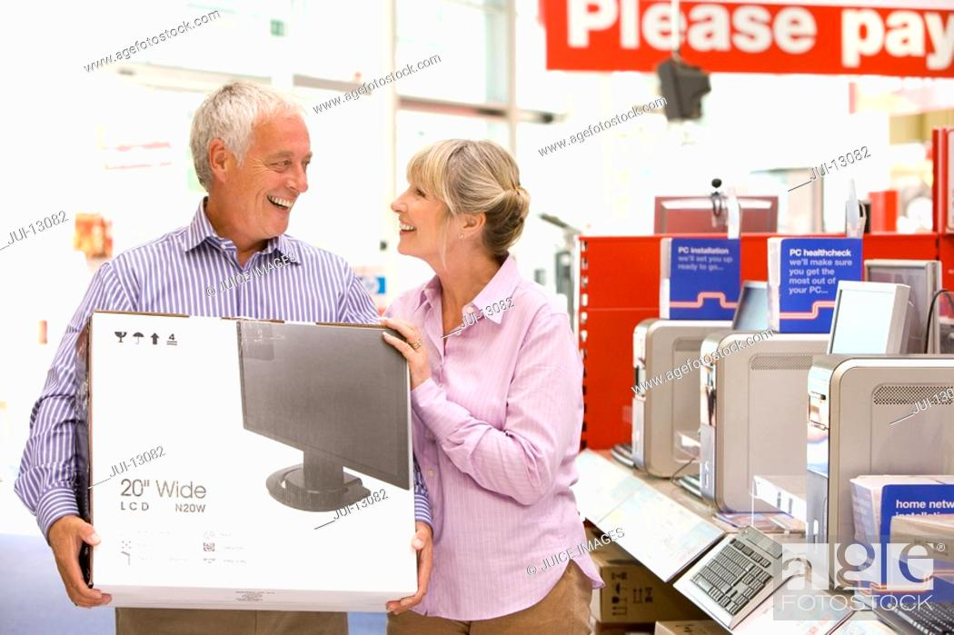 Stock Photo: Mature couple shopping, man holding computer in box, smiling at each other.