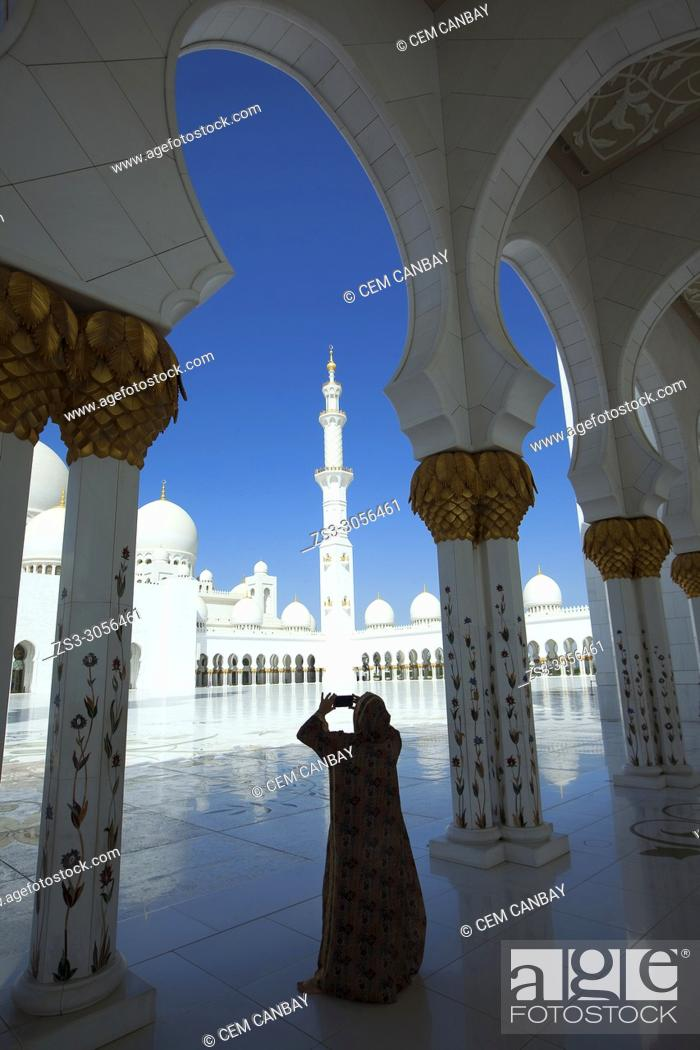 Stock Photo: Visitor with headscarf taking photos between the gilded columns of Sheikh Zayed Bin Sultan Al Nahyan Mosque, Abu Dhabi, United Arab Emirates, Middle East.