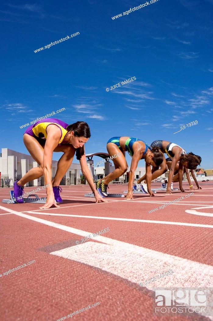 Stock Photo: Female runners at starting block kneeling on race track.