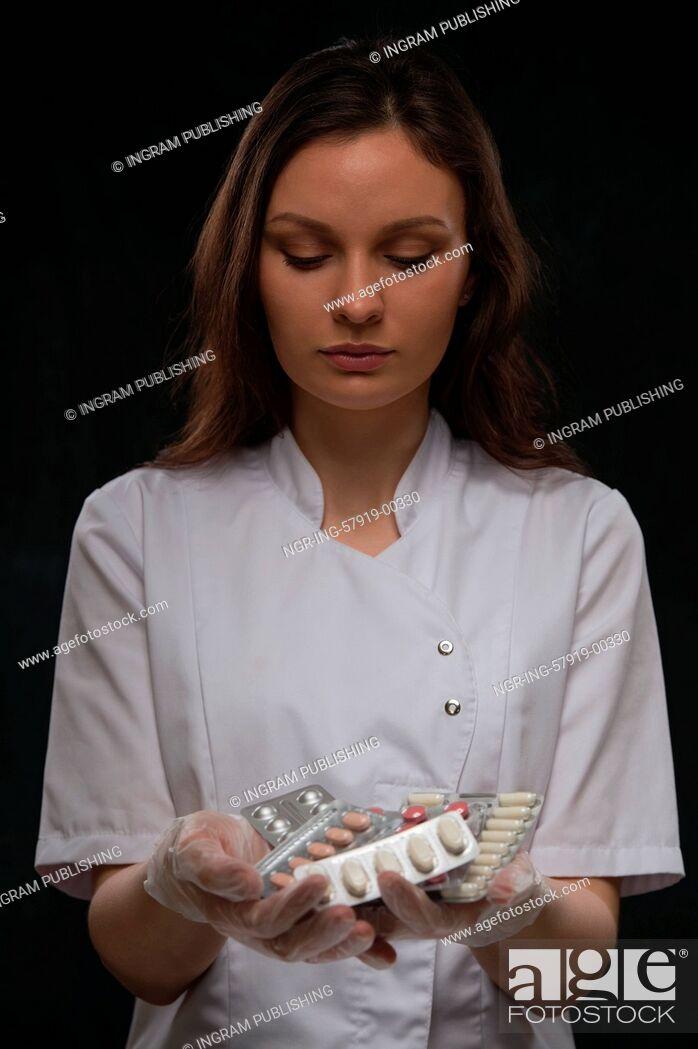 Stock Photo: Female doctor holding a stack of many different pills.