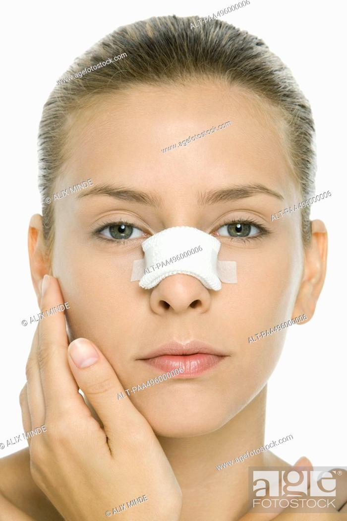 Stock Photo: Woman with bandaged nose, looking at camera, portrait.