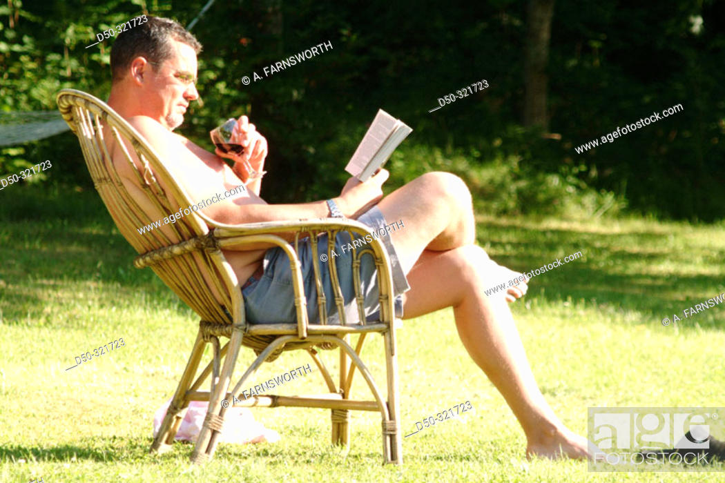 Stock Photo: Man relaxes with a book and a glass of wine in the sun. Sweden.