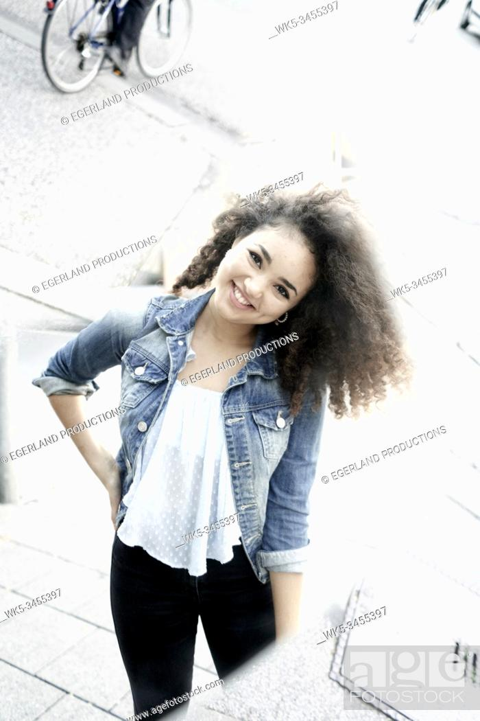 Stock Photo: Young hispanic woman on the street, reflected in mirror. Munich, Germany.