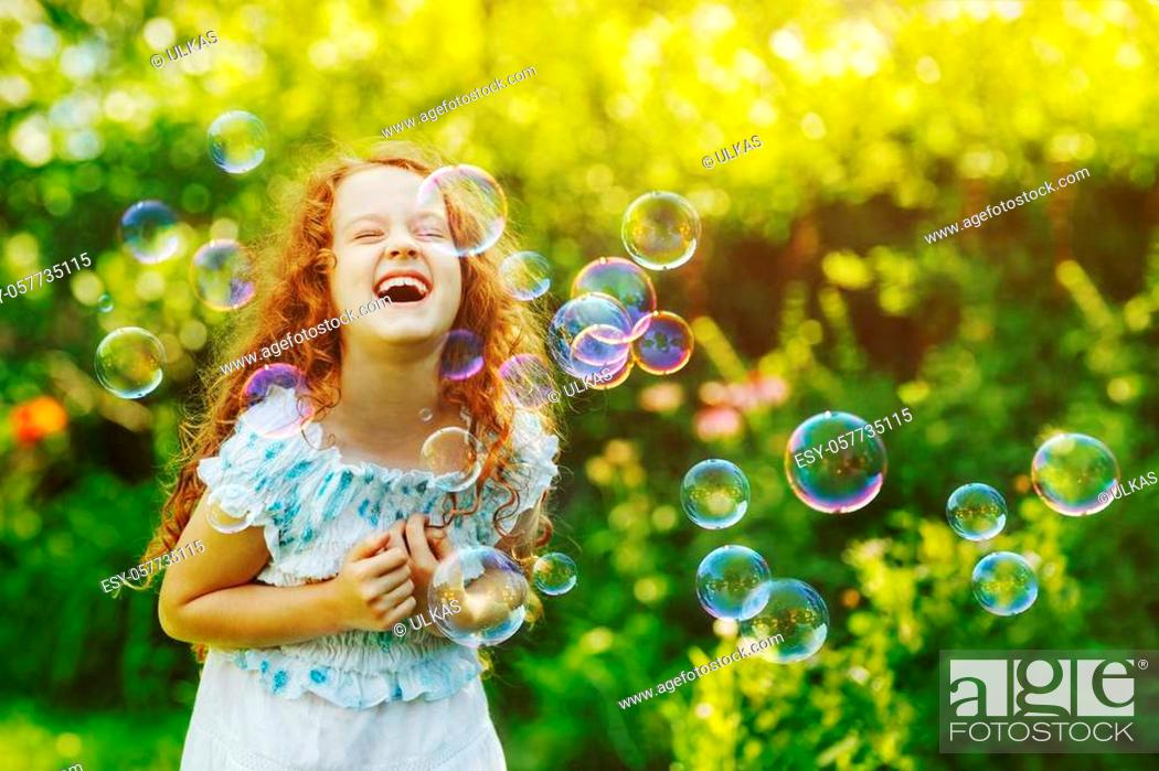 Stock Photo: Laughing curly girl with bubbles. Happy childhood concept.