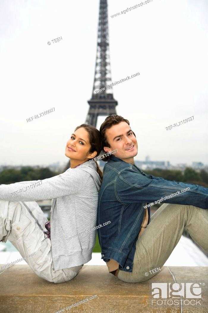 Stock Photo: Young couple sitting back to back with Eiffel tower in background, Paris, France.